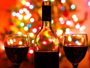 Bottle of red wine with Christmas lights in the background