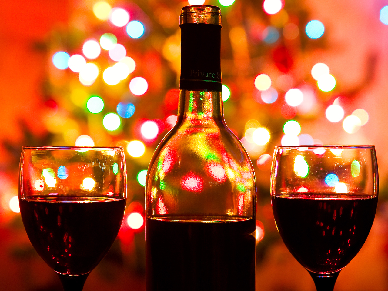 image a bottle of red wine with christmas lights in the background - Wine Christmas